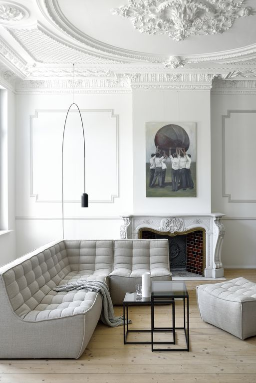 an all-white living room with a light grey sofa and some touches of black for a bit of drama