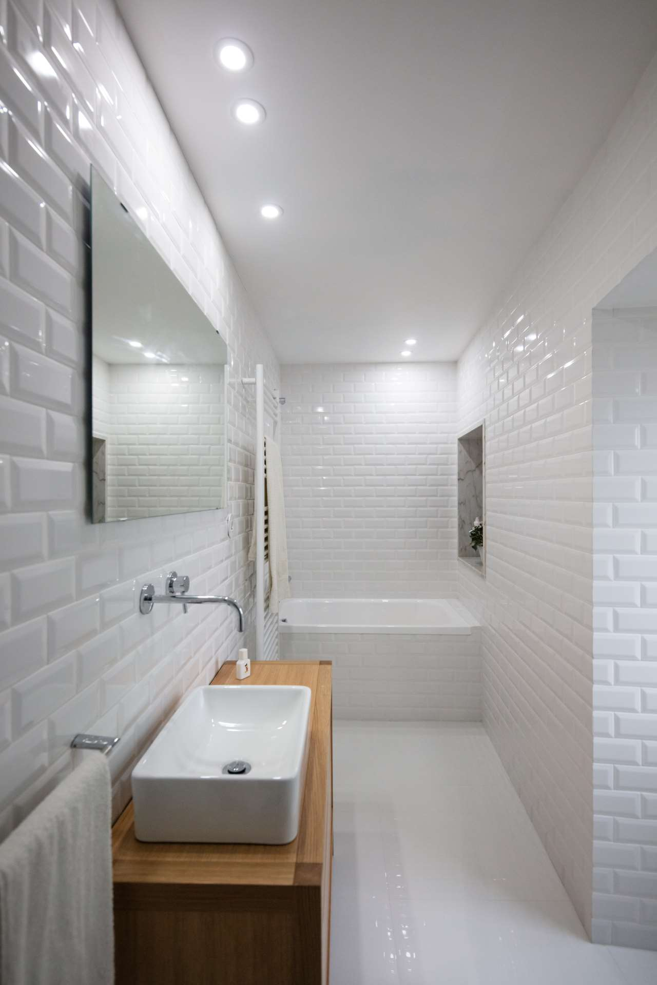 The bathroom is fully done in white, with chic tiles, a wooden vanity and a built in bathtub