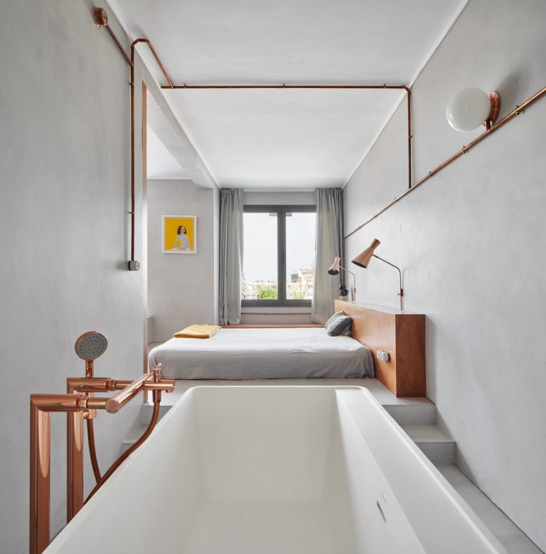 The bathroom is placed next to the bedroom, with a bathtub and elegant hardware