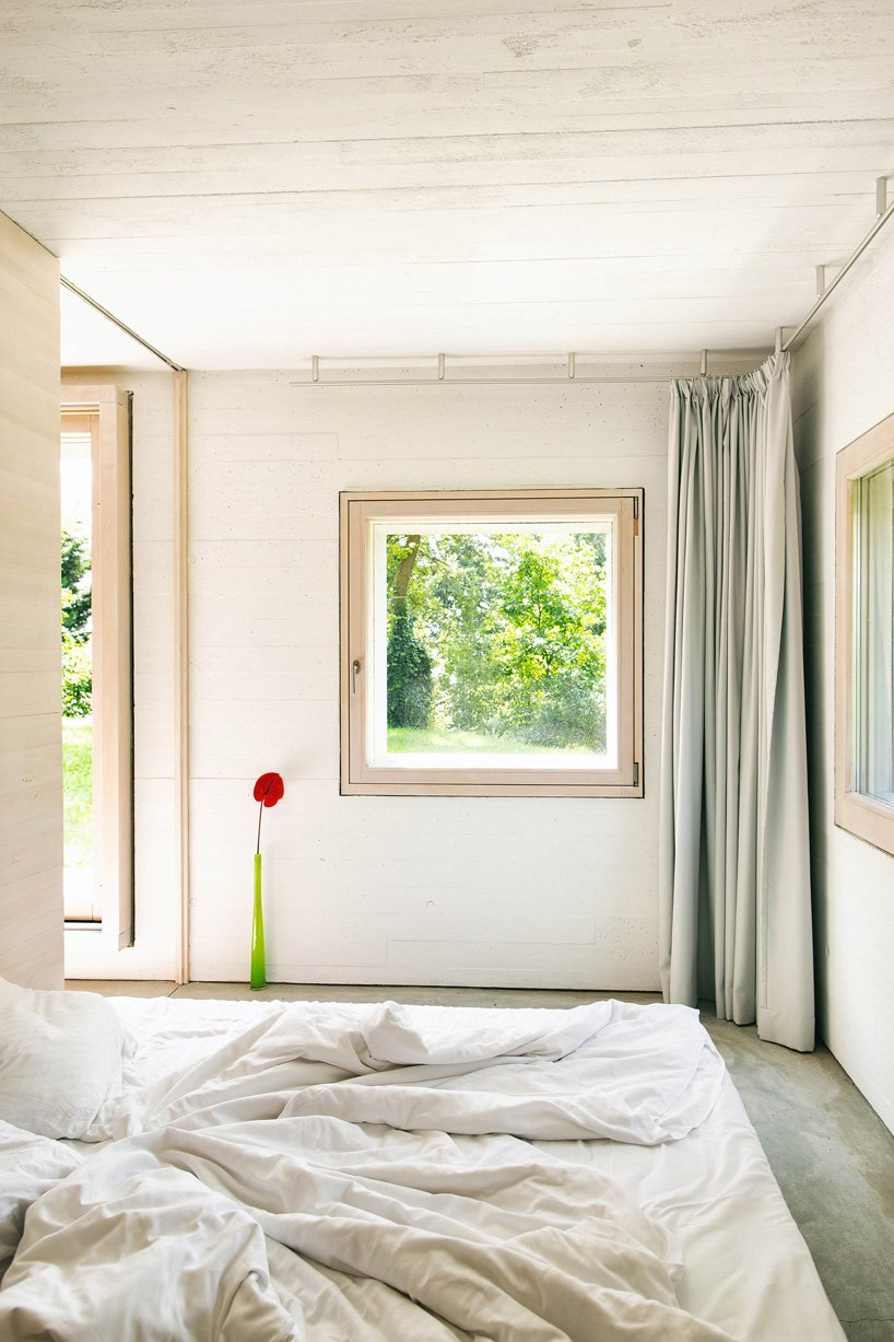 The bedroom is done with large windows and a comfortable bed, nothing else
