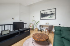 07 The living room is combined with a home office, there's a statement green sofa, a blush rug, a catchy table and a TV