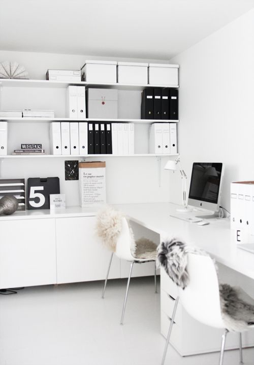 a contemporary white home office with open shelving, cabinets and a white shared desk for working