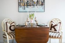 07 a drop leaf wooden dining table on catchy curved legs and white vintage chairs make up a stylish dining nook