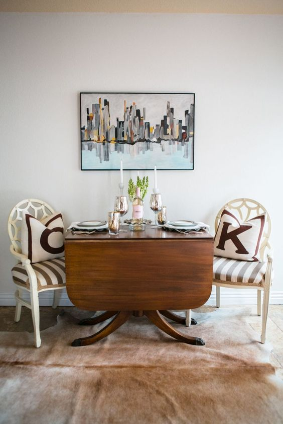 a drop leaf wooden dining table on catchy curved legs and white vintage chairs make up a stylish dining nook