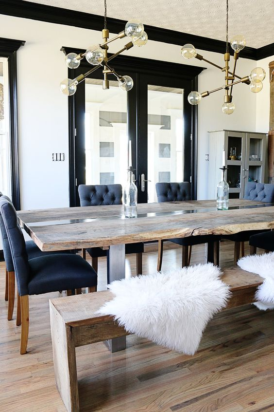 a live edge dining table and a matching reclaimed wood bench contrast the chic blue chairs