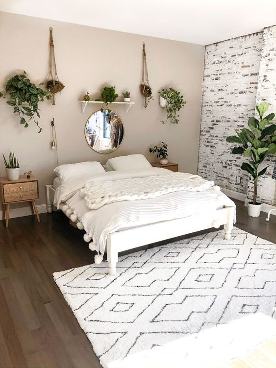 a neutral boho minimalist bedroom in white and greys plus light-toned wooden furniture
