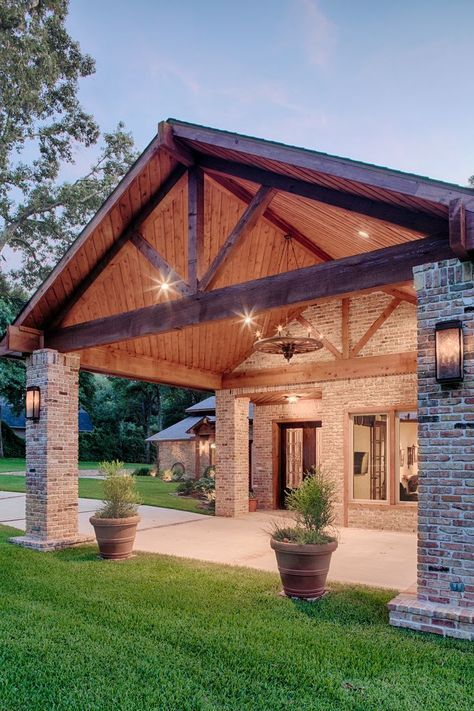 a stylish barndominium with brick pillars and a classic gabled roof with beams that feels very cozy and rustic