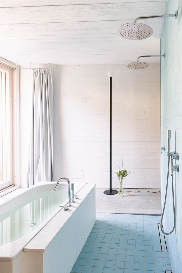 The bathroom is done with white and neutral tiles and concrete, and there's a bathtub