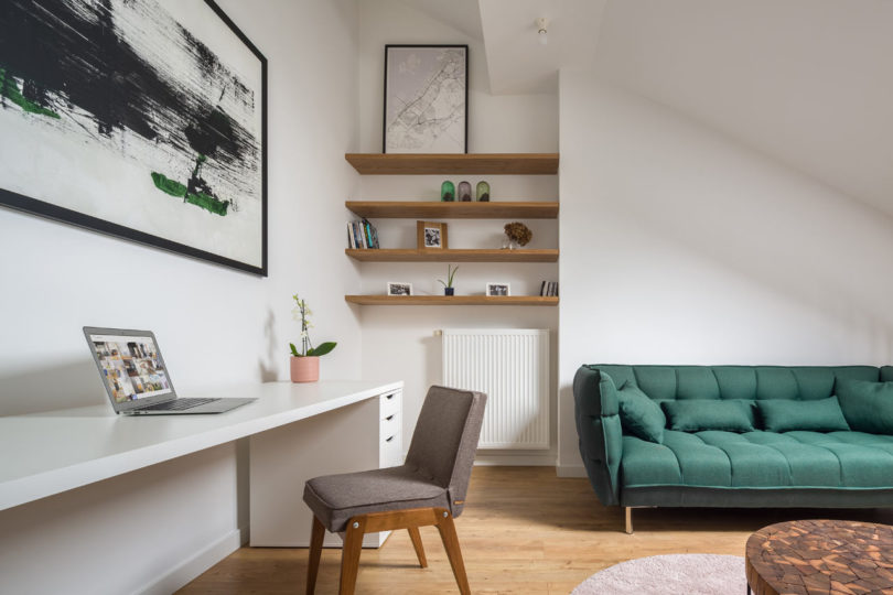 The home office space features a large white desk, a grey chair and some open shelves taking an awkward corner