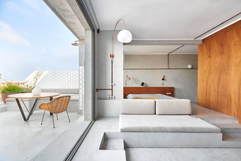 The terrace continues the decor of the spaces, with grey furniture and rattan items