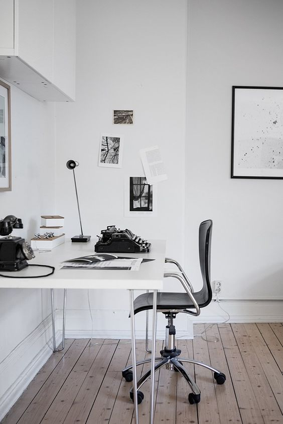 a contemporary white home office with touches of black and vintage items to give it a character