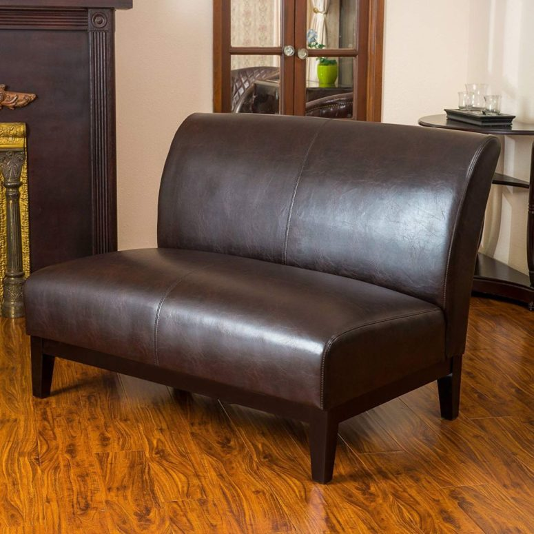 a loveseat of brown leather, with stained wooden legs will make an accent not only with its look but also with a texture