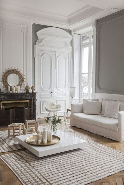 a neutral Parisian living room with light-colored wood parquet floors that are covered with striped rugs