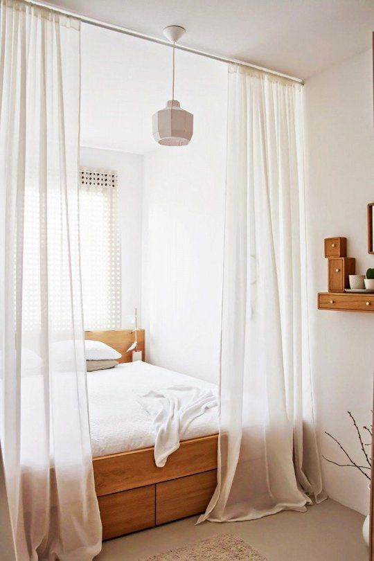 a sheer white curtain is a perfect option to separate a sleeping space from the rest of your apartment