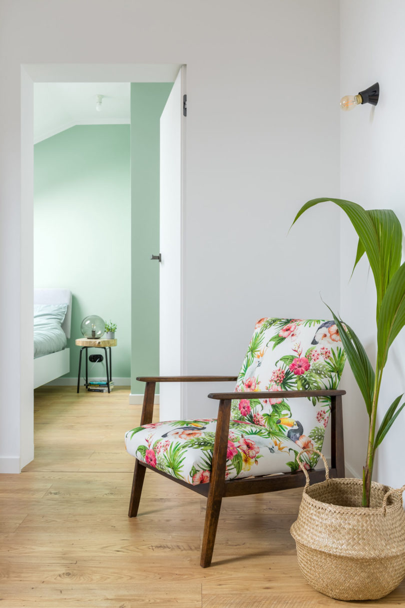 A bright floral chair cheers up the living room and helps it transition into the bedroom