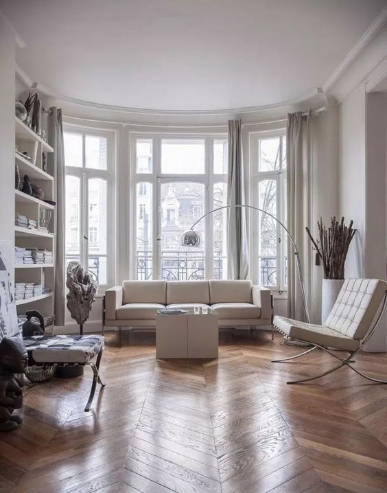 a contemporary Parisian living room with all-whites and a hardwood parquet floor to soften the space