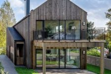 09 a contemporary yet rustic barndominium with glazed walls and a terrace on the upper floor