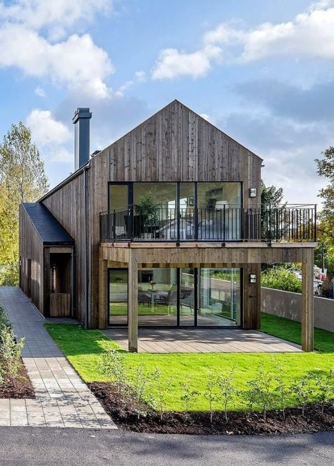 a contemporary yet rustic barndominium with glazed walls and a terrace on the upper floor