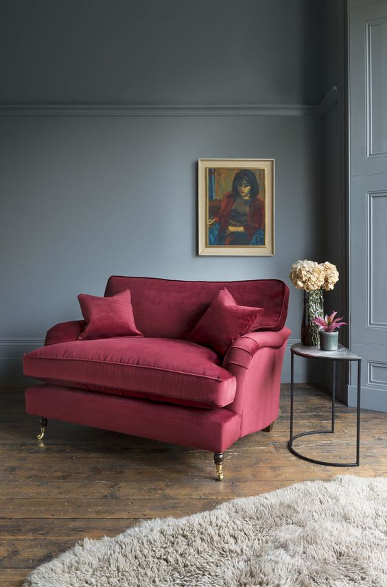 a moody living room with a burgundy loveseat and pillows, a grey faux fur rug for polishing the look