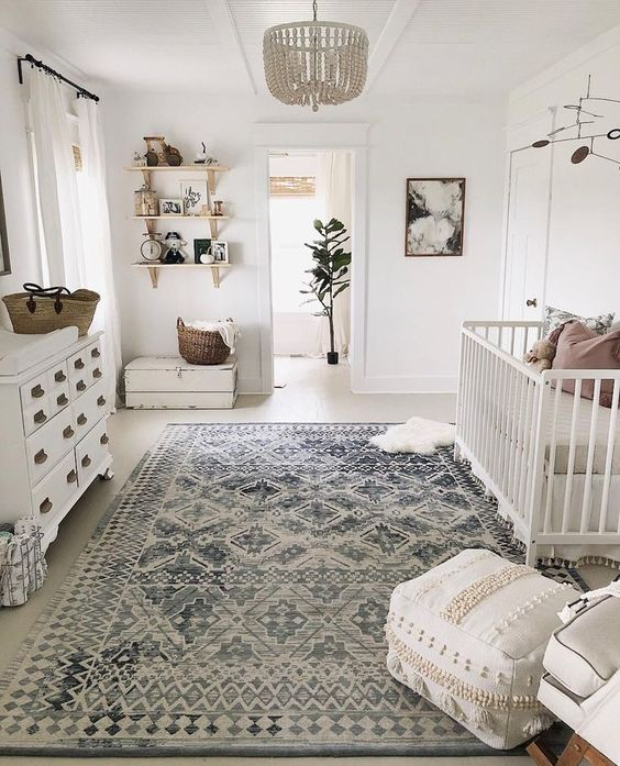 a neutral famrhouse meets boho nursery with a beaded chandelier, a Moroccan blanket ottoman and baskets