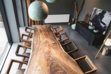 09 a super eye-catchy dining table made of a live edge slab and catchy geometric chairs plus teal pendant lamps over the table