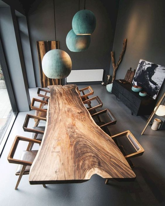a super eye-catchy dining table made of a live edge slab and catchy geometric chairs plus teal pendant lamps over the table