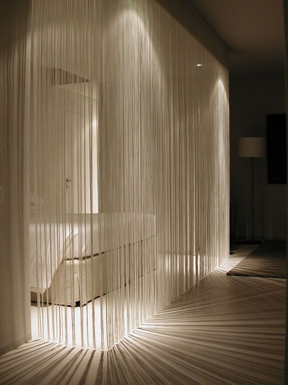 a white fringe curtain is a cool take on a usual white sheer curtain, it divides spaces and doesn't look obtrusive