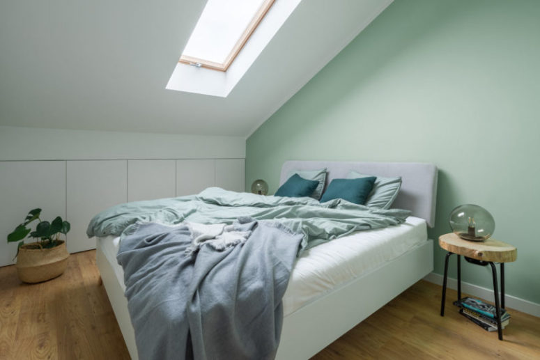 The bedroom is soothing, with a skylight, an upholstered bed and a larrge storage unit hidden behind sleke panels