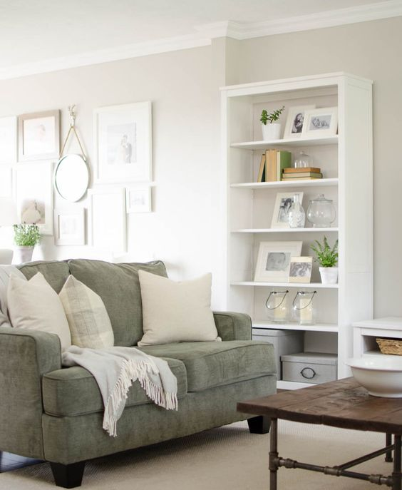 a muted green loveseat with neutral pillows matches the modern famrhouse decor of the living room