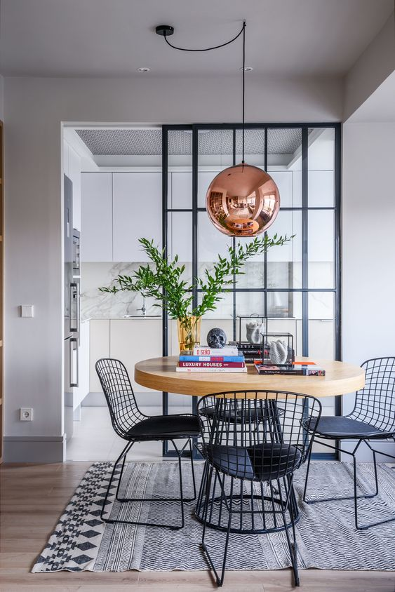 a stylish dining space with a round table on a metal base and matching black metal chairs plus a copper pendant lamp