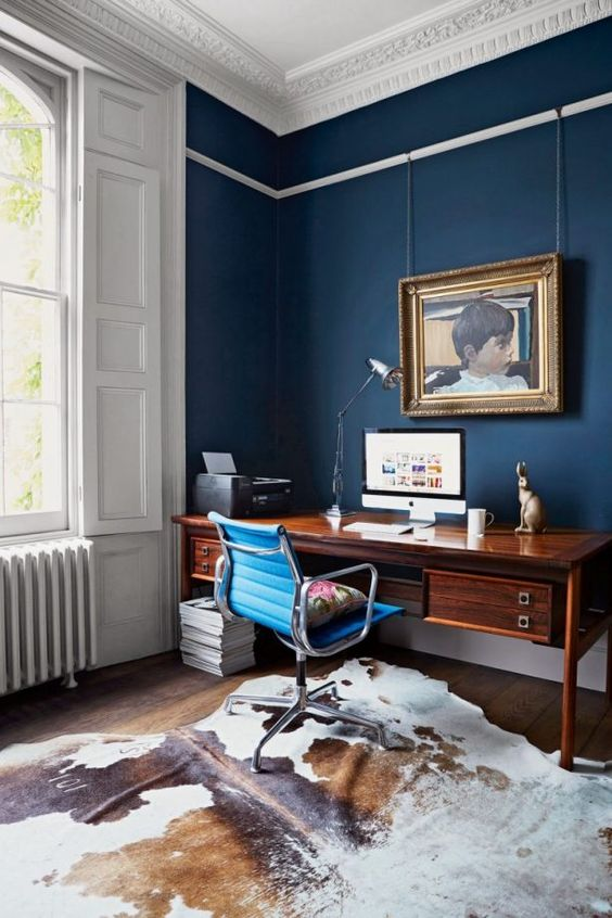 a stylish home office with navy walls, stucco, a vintage wooden desk and an animal skin rug