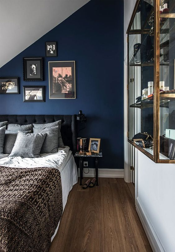 an epic navy attic bedroom with a dark upholstered bed, neutral bedding and a glass wall cabinet