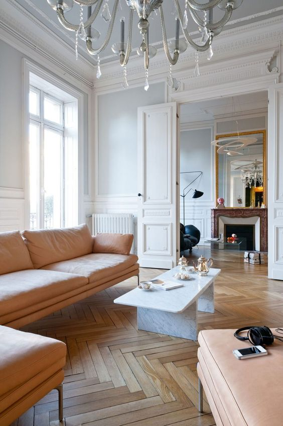 pair white walls and hardwood parquet floors adding soft peachy furniture to soothe the space