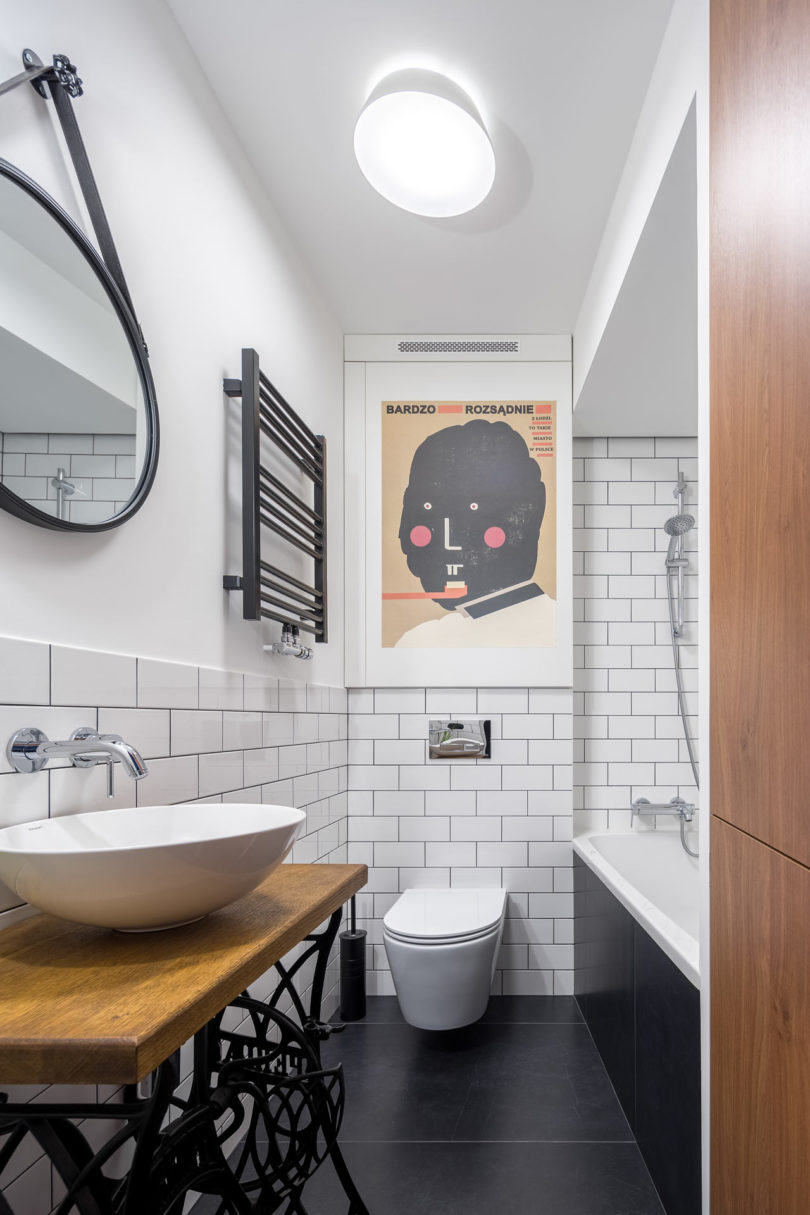 The bathroom is done in black and white, with an artwork, a unique vanity of a Zinger sewing machine and subway tiles