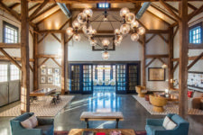 11 a beautiful barndominium space with wooden beams, exposed pipes and a statement chandelier plus muted touches of color