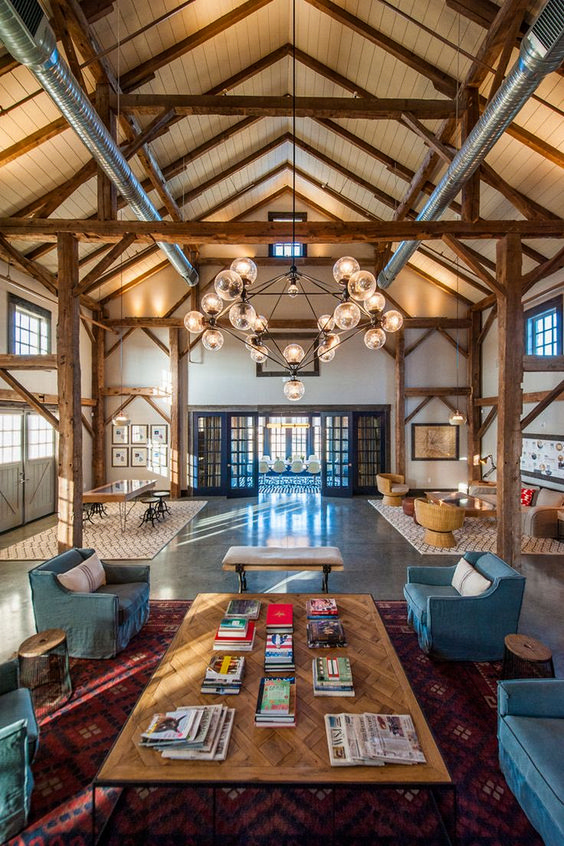 a beautiful barndominium space with wooden beams, exposed pipes and a statement chandelier plus muted touches of color