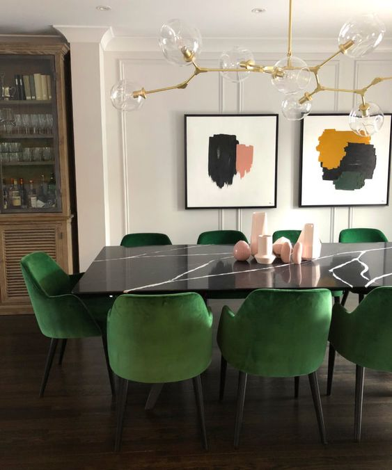 a dining table of black stone and emerald chairs to contrast and highlight the dark tabletop a lot