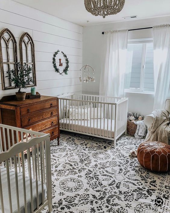 a farmhouse meets boho nursery with stained wooden furniture, a leather ottoman, a printed rug and greenery