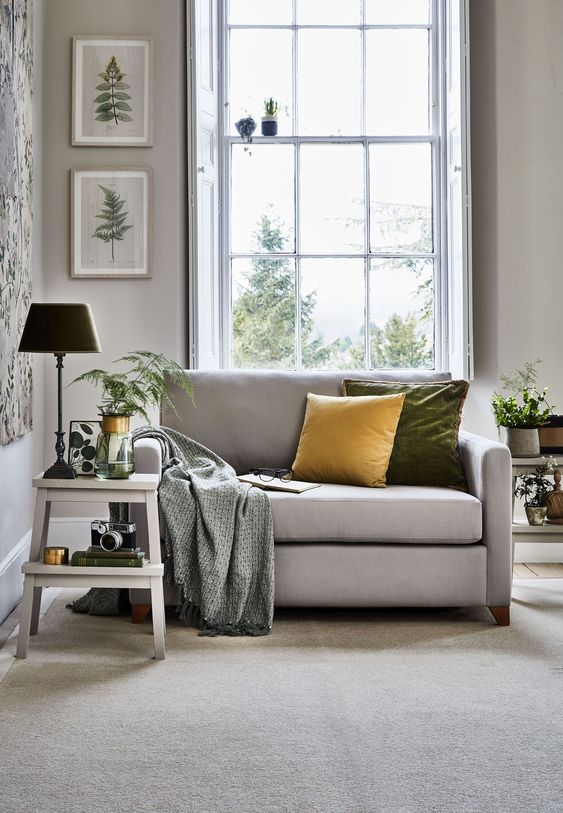 a neutral grey loveseat with colorful pillows and a printed blanket is an ideal piece for your cozy reading nook