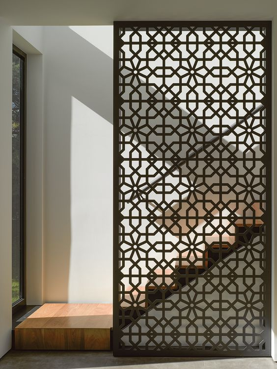 a sheer laser cut screen of Douglas fir is a stylish way to divide spaces and accent them a bit