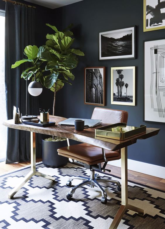 navy walls, curtains and pots set the tone of the home office, and a wooden desk and leather chair soften it
