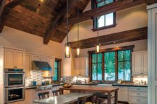 12 a barndominium kitchen and dining space with a ceiling with wooden beams and suspended lamps