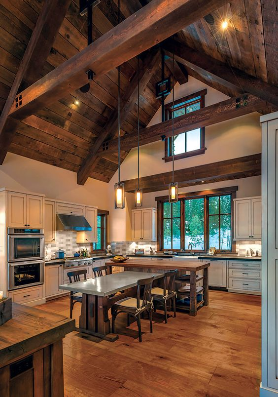 a barndominium kitchen and dining space with a ceiling with wooden beams and suspended lamps