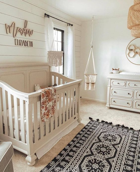 a traditional rustic nursery with boho elements like rugs, textiles and a wicker lampshade