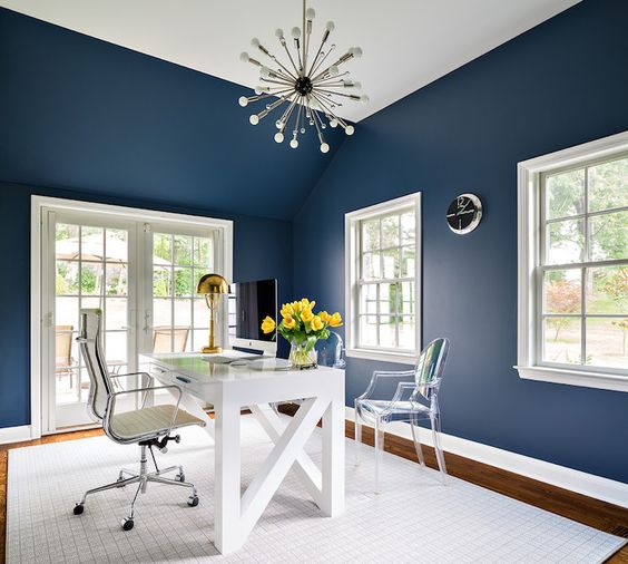 a clean home office with navy walls is given much negative space and light to avoid boring and dark looks