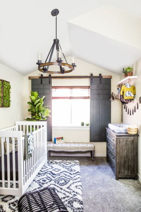 a cozy rustic nursery with a tassel garland, printed rugs, a wooden plank ottoman and much greenery