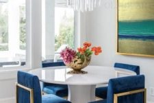 13 a white geometric table with a round tabletop makes the bright blue chairs stand out a lot