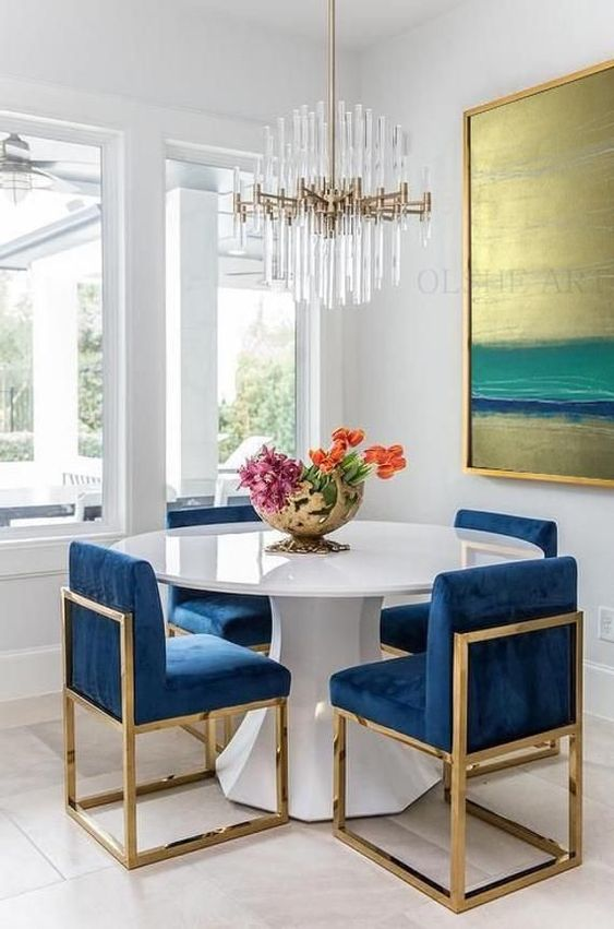 a white geometric table with a round tabletop makes the bright blue chairs stand out a lot
