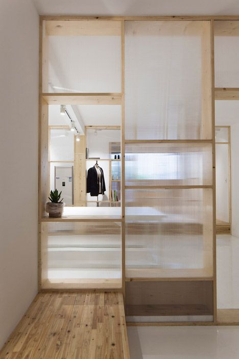 a wood and frosted glass room divider with plenty of storage doesn't look bulky and provides storage
