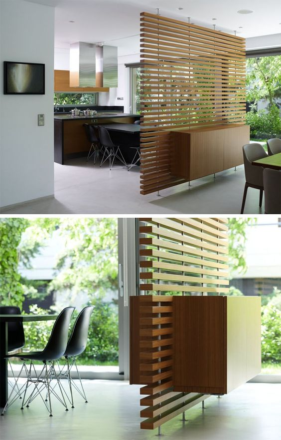 a contemporary slatted wood room divider with a cabinet integrated for storage is sheer enough for a small space